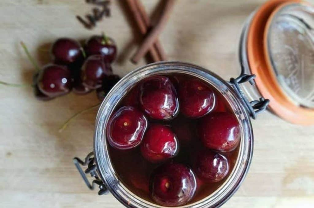 Jar filled with a delicious brandied cherry recipe.